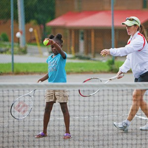 woman teaching girl tenis